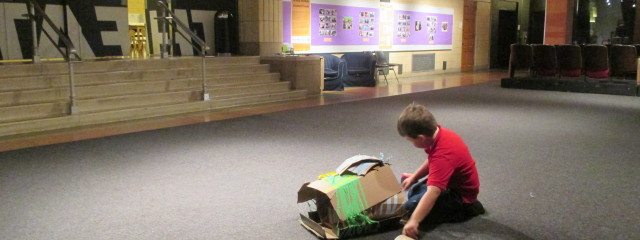 A boy sits with his recycled materials project in a large room