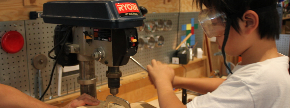 A boy using a drillpress to create holes