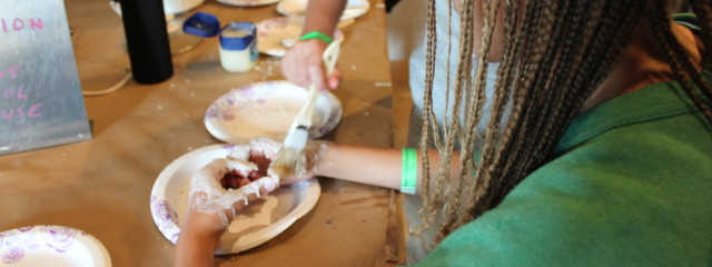 Wax being spread on a Youth Maker's hands.