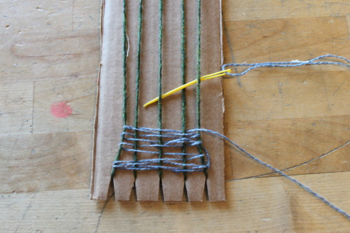 A plastic needle weaving a weft on the cardboard loom