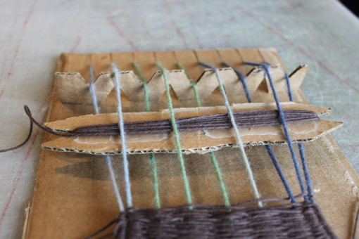 The cardboard loom with cardboard heddle, even-numbered string lifted