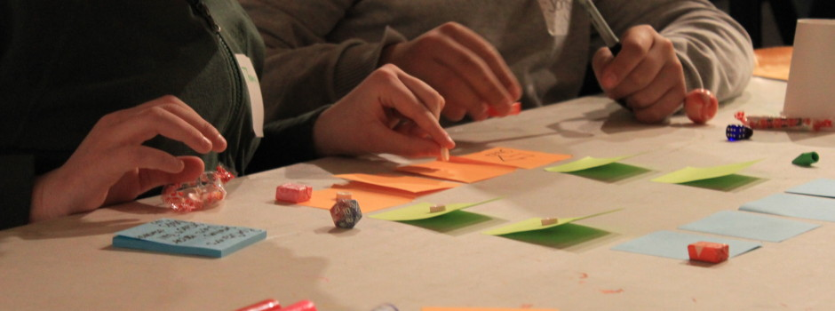 Kids work on a post-it note based board game design