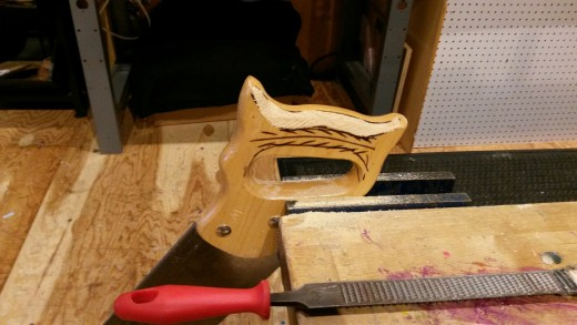 A saw held in a vice, with a rasp nearby. The handle is beginning the reshaping process.