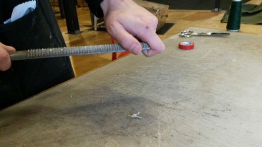 The same as above -- a hand holding a rasp -- but this time a second hand stabilizes the other end of the tool