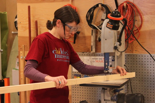 Melissa uses a bandsaw to cut wood.