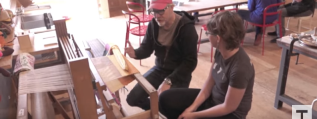 Adam Savage sits at a loom with a MAKESHOP employee