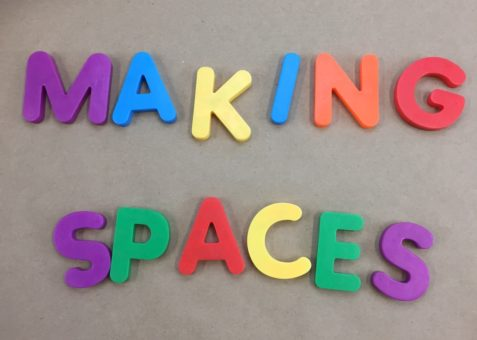 Colorful magnetic letters that read MAKING SPACES on a brown background